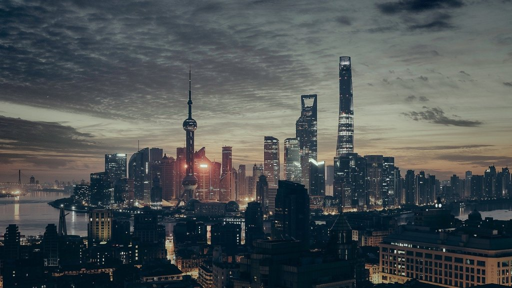 Image of shanghai at dusk. Many people come to cities for jobs and tall office buildings are a feature of cities.